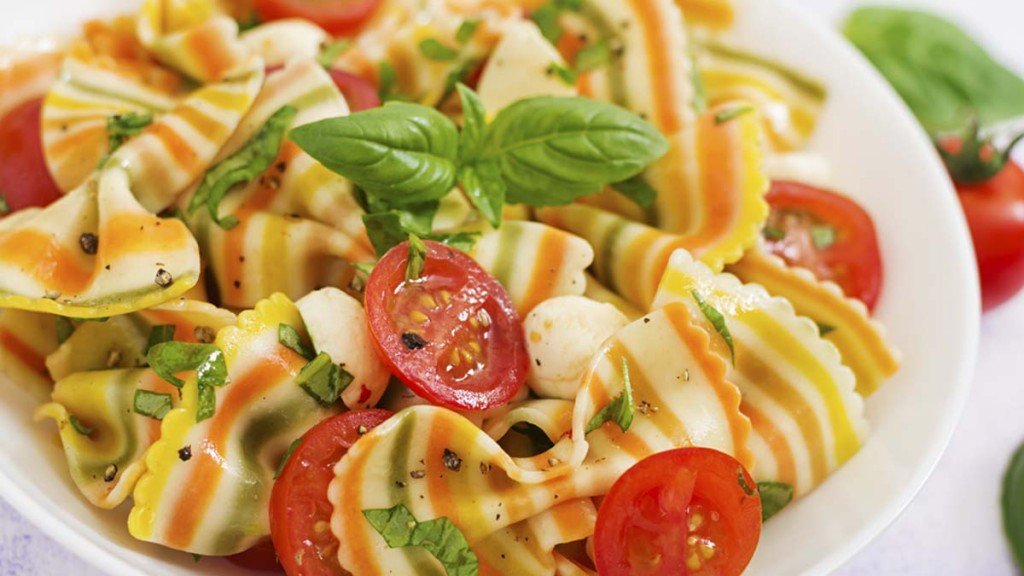 Pasta colored farfalle salad with tomatoes, mozzarella and basil